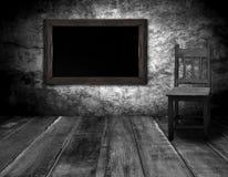 黑板和木头椅子在有灰色木墙壁的内部屋子里 库存照片