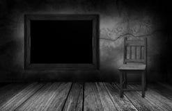 黑板和木头椅子在有灰色石墙的内部屋子里 库存图片