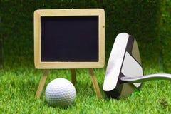 黑板和高尔夫球在绿色背景 库存照片