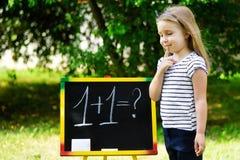 黑板实践的计数和算术的可爱的滑稽的小女孩 库存图片