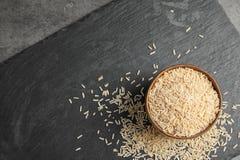 板岩板材用在碗的未加工的未磨光的米在桌,顶视图上 库存照片