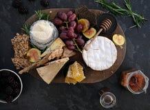 板岩表面上的木cheeseboard用各种各样的乳酪、薄脆饼干、果子、蜂蜜、迷迭香小树枝和酸辣调味品 免版税库存图片