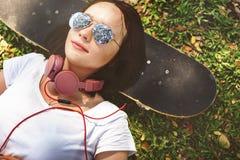 滑板放松休息说谎的寒冷的耳机概念 库存图片