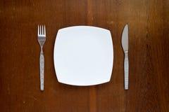 板材、叉子和刀子在木背景 免版税图库摄影