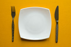 板材、叉子和刀子在黄色背景 免版税图库摄影