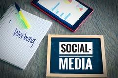 板材有题字社会媒介的和用在英国广告的德语Werbung以象征da的片剂和blockto 免版税库存图片