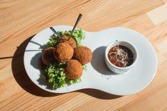 板材特写镜头用西班牙炸丸子服务用沙拉和调味汁 免版税库存照片