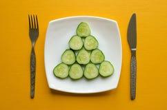 板材用切的黄瓜、叉子和刀子 免版税库存图片