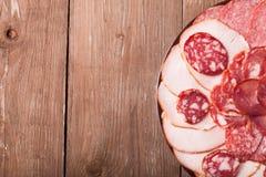 板材用在一张老木桌上的另外切的香肠 与 库存照片