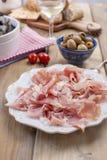 板材用在木背景的肉,绿橄榄 免版税库存图片