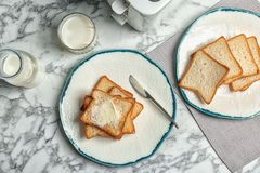 板材用敬酒的面包和新鲜的牛奶在桌上 免版税库存图片
