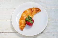 板材用新月形面包和草莓 免版税库存照片