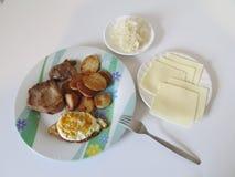 板材用煮熟的土豆、肉、鸡蛋在板材旁边用乳酪和sauecraut 库存照片