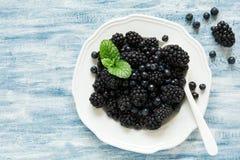 板材用黑莓和蓝莓在蓝色木背景 库存图片