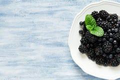板材用黑莓和蓝莓在蓝色木背景 免版税库存照片