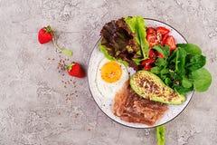 板材用keto饮食食物 荷包蛋、烟肉、鲕梨、芝麻菜和草莓 免版税库存图片