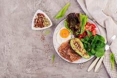 板材用keto饮食食物 荷包蛋、烟肉、鲕梨、芝麻菜和草莓 库存图片