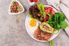 板材用keto饮食食物 荷包蛋、烟肉、鲕梨、芝麻菜和草莓 图库摄影