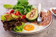 板材用keto饮食食物 荷包蛋、烟肉、鲕梨、芝麻菜和草莓 免版税图库摄影