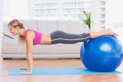 板条位置的亭亭玉立的金发碧眼的女人使用锻炼球 免版税库存照片