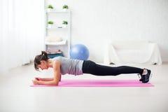 板条位置的适合的女孩在席子在家后面脊椎和姿势概念pilates健身的客厅锻炼 图库摄影