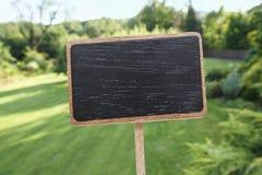 黑板标签和一个美丽的庭院 免版税库存照片