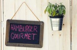 黑板汉堡包食家和罐有植物的木表面上 免版税图库摄影