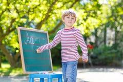 黑板的学会的小男孩写 库存照片