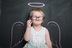 黑板的小女孩有翼和光晕的 免版税图库摄影