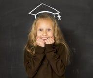 黑板的甜女小学生有有白垩略图的毕业帽子微笑愉快 免版税库存照片