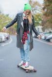 滑板的年轻白人妇女在街道 免版税库存图片