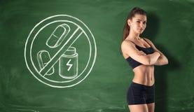 黑板背景的健身女孩有禁止干燥蛋白质和药片的标志的 免版税库存图片
