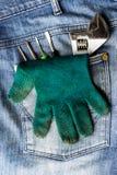 板钳、手套和一把螺丝刀在牛仔裤 免版税库存图片