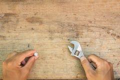 板钳和手在棕色木背景 图库摄影