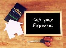 黑板顶视图有口号的切开了您的费用剪刀,有信用卡的钱包并且安置形状的纸 家庭或 库存照片