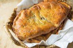 极为愉快家庭焙制的意大利酥皮点心Calzone用填装在白色亚麻布餐巾的柳条筐的甜苹果饼葡萄干桂香 图库摄影