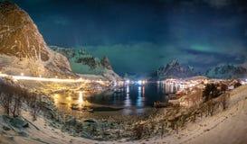 极光borealis全景在斯堪的纳维亚村庄的在冬天 库存图片