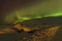 极光Borealis和在雪的一辆汽车 免版税库存图片