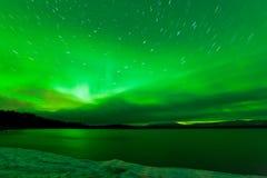 极光borealis在湖Laberge的繁星之夜天空 库存照片