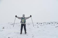 极其体育运动 站立在与被上升的hads的上面的冬天山的孤立远足者 库存图片
