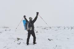 极其体育运动 站立在与被上升的hads的峰顶的冬天山的孤立远足者 图库摄影