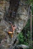 极其体育运动 年轻运动男性攀岩运动员上升的峭壁墙壁 复制在右边的空间 免版税库存图片
