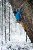 极其体育运动 年轻运动男性攀岩运动员上升的峭壁墙壁 库存照片