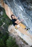 极其体育运动 年轻运动男性攀岩运动员上升的峭壁墙壁 免版税库存照片