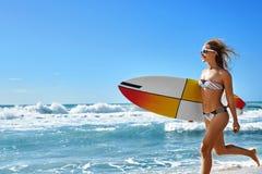 极其水上运动 冲浪 有冲浪板海滩赛跑的女孩 免版税图库摄影