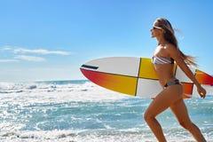 极其水上运动 冲浪 有冲浪板海滩赛跑的女孩 免版税库存图片