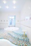 极可意浴缸和台阶在宽敞白色卫生间里 库存图片