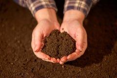 极少数可耕的土壤在负责任的农夫的手上 免版税库存图片