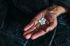 极少数白色片剂或药片在一名年长妇女的手上 免版税库存照片