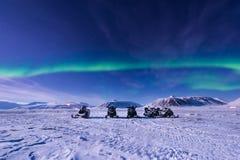 极性北极雪上电车北极光极光borealis天空星在朗伊尔城市月亮山的挪威斯瓦尔巴特群岛 免版税库存图片